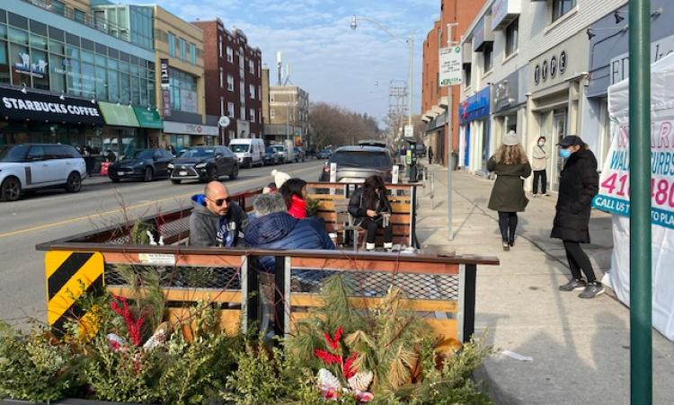 People sitting on benches enjoying the parklet on Spadina Rd.
